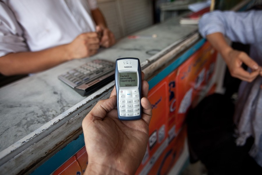 A man holds a phone at a mobile money kiosk.