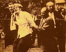White man - Bruce Beyer - is being led away from a crowd with hands handcuffed behind his back.