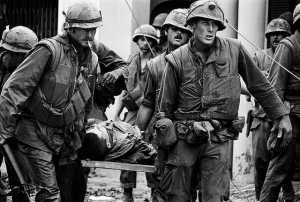 Image of soldiers carrying a man on a stretcher. Black and white, vietnam war.