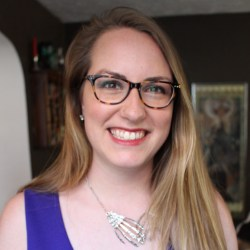 Headshot of Sarah Handley-Cousins, dark blonde haired white woman wearing tortise shell glasses, pink lipstick, a skeleton hands necklace, and a purple sleeveless dress.