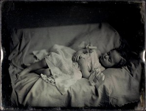 Black and white photograph of a toddler laying on her back, tilted toward the camera, with hands on her belly, looking asleep.
