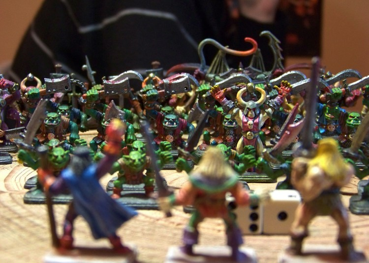 Small plastic models of fighting warriors, monsters, and other creatures, with two playing dice in the center