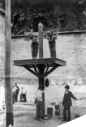A black and white photograph that shows two men in stocks on a high plaform. Beneath it, a man with his shirt off is about to be whipped.