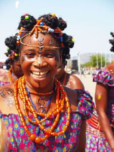 A colorful photograph of a woman wearing paint on her face and many orange necklaces, smiling