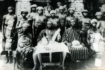 A black and white photo of a Igbo man surrounded by many women