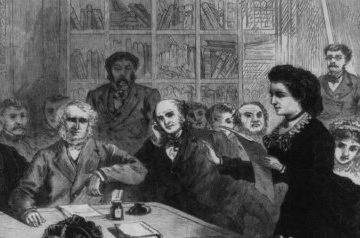A black and white engraving of people crowded around a table while a woman dressed in black and standing speaks from a prepared text