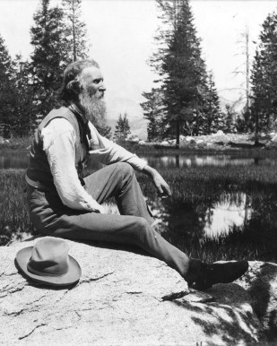 A black and white photograph of John Muir outside in nature