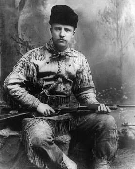 a black and white photograph of theodore roosevelt as a young man wearing buckskin clothing