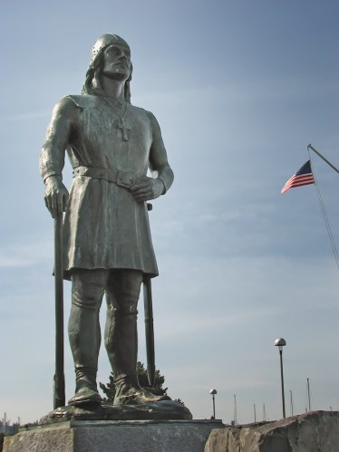 A color photograph of a statue of a Viking with a blue sky background