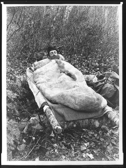A photograph showing a man laying down in a sleeping bag made from animal skin