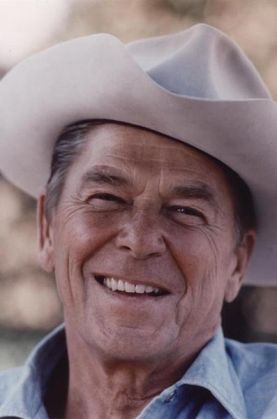 A picture of a smiling Ronald Reagan wearing a light colored cowboy hat