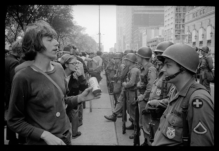 """Young """"hippie"""" standing in front of a row of National Guard soldiers, across the street from the Hilton Hotel at Grant Park, at the Democratic National Convention in Chicago, August 26, 1968"""