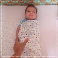 Prenda um dos braços do bebê ao longo ou sobre o corpo, e enfie a ponta do tecido embaixo do bebê