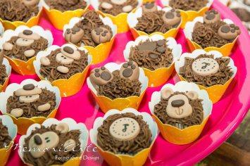 Cupcakes decorados de urso com capinha amarela numa bandeja rosa foram o destaque da festa.