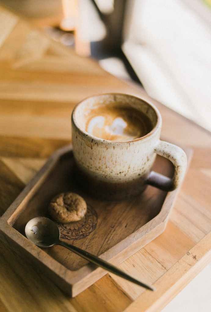 spoon with cookie by cup of coffee