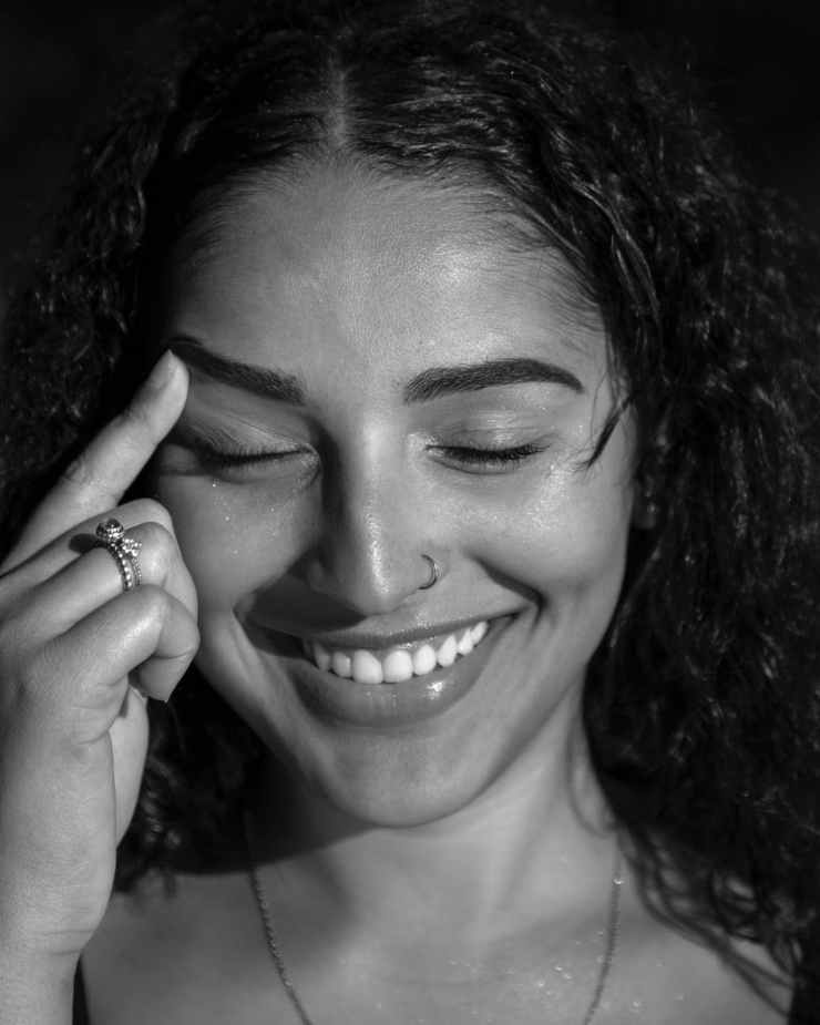 monochrome photo of smiling woman touching her eyebrow