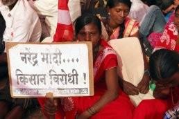 A group of young women with placards, wearing the same colours as the flag. The emblem on the flag was also on their saree borders