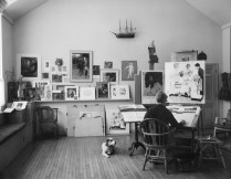 Norman Rockwell works in his studio with dog, Pitter, at his side.