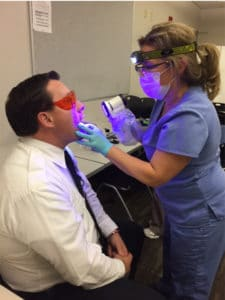 Firefighter Lisa Evans, RDH, BA, EMT, conducts an oral cancer screening
