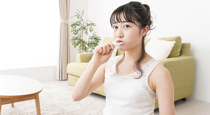 Young woman brushing a tooth