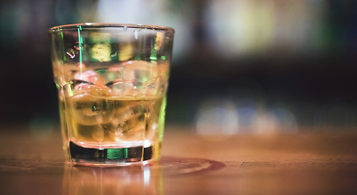 lose up shot of a tumbler glass with whiskey on the rocks.