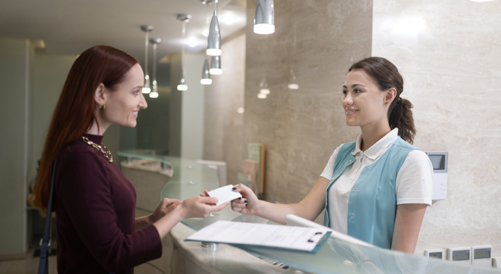 Smiling receptionist of dentistry giving contact details for client
