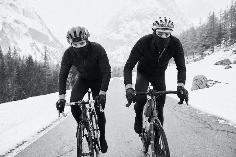 Deux cyclistes roulent dans un paysage enneigé