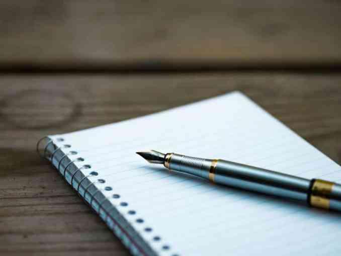 foto gambar buku dengan bolpoin atau pensil diatasnya, alat tulis