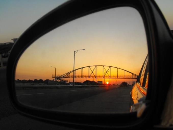 foto kaca spion, terlihat jembatan dan lampu jalan saat senja