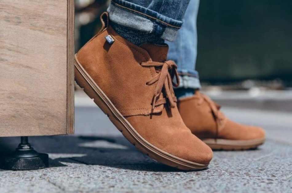 kaki pria yang menggunakan celana jeans dan memakai sepatu chukka coklat sedang berdiri diatas aspal dengan satu kaki menyender pada kayu