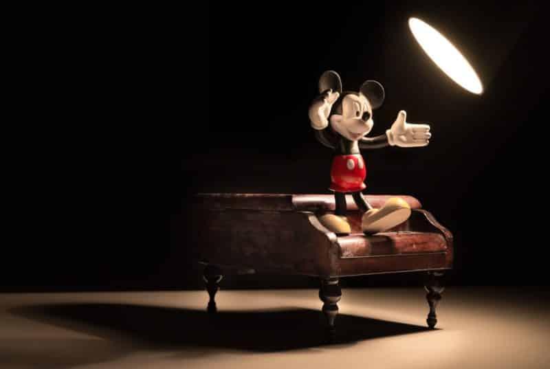 foto keren untuk profil whatsapp instagram telegram tiktok facebook line karakter kartun miniatur mickey mouse di atas piano kayu di panggung dengan lampu sorot di kegelapan