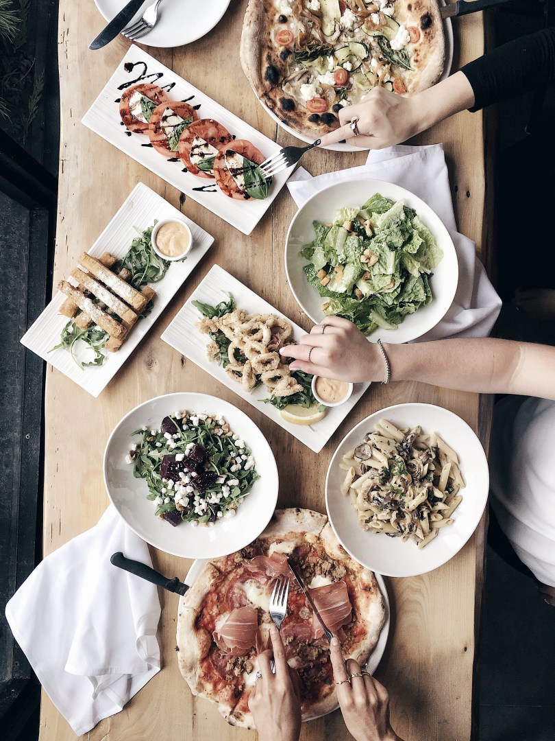 An aerial view of our feast at Lambretta Pizzeria, including calamari, caprese salad, vegetarian and meat pizzas, caesar salad and penne pasta