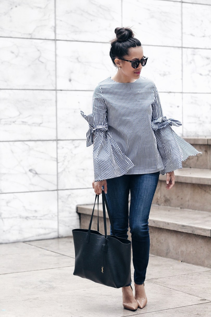 Pairing this striped bell sleeve top with blue denim, black Moschino sunglasses, and a Saint Laurent tote