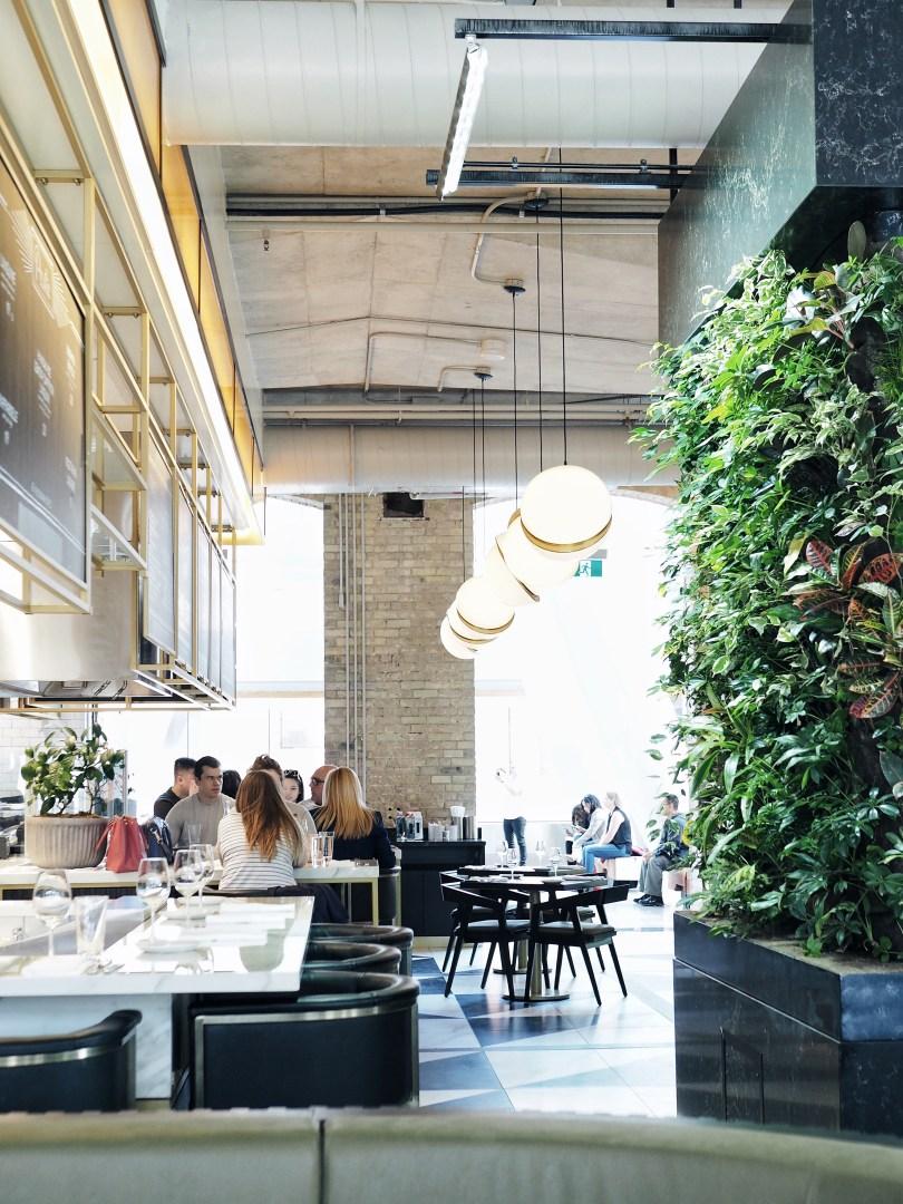 Greenery wall and interior at Ricarda's Toronto