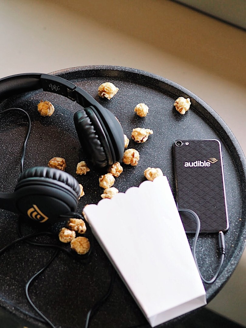Flatlay of popcorn and audible headphones and ipod