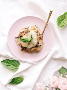 Beautiful eggplant lasagna served in pink plate with gold fork