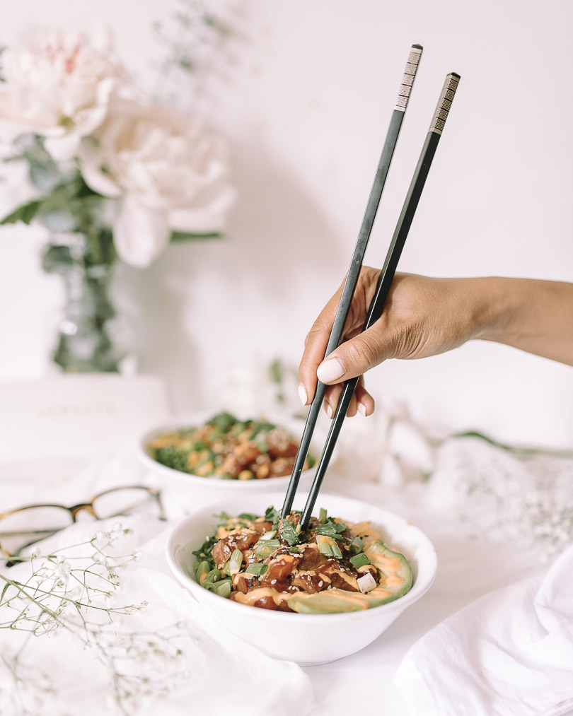 Using chopstick to eat salmon poke bowl