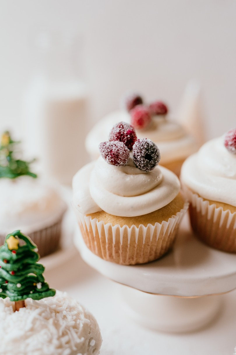 vanilla holiday cupcake topped with sugared cranberries