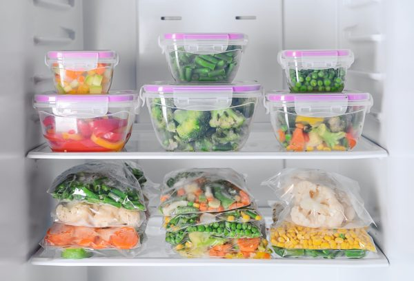 Containers and plastic bags with frozen vegetables in refrigerator