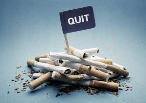 "pile of cigarettes with a black flag that says ""quit"""