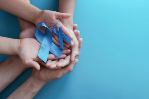 two hands along with two prostate cancer ribbons. family history awareness concept