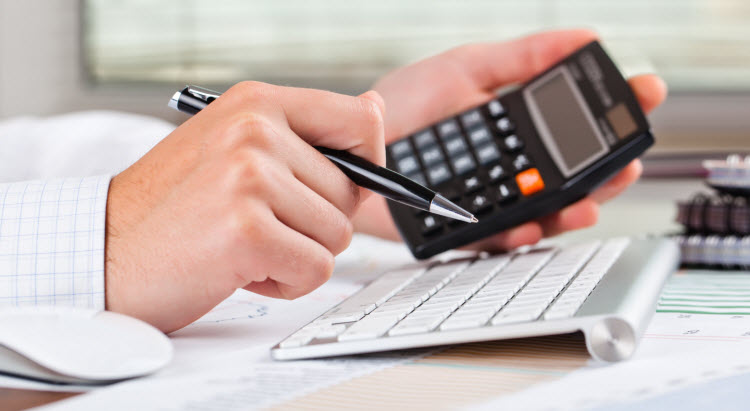 business person adding the numbers on a calculator