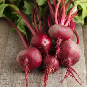 Harvest of fresh beetroot (Beta vulgaris) on a wooden background