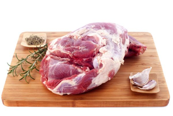 raw shoulder of lamb on a cutting board