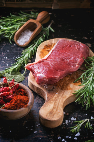 Raw steak on olive cutting board with rosemary herbs and red hot pepper over black wooden table. See series