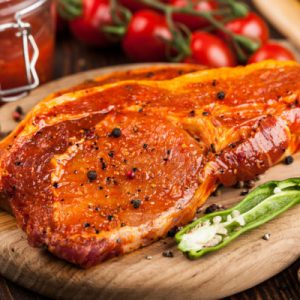 Marinated pork steaks on cutting board and ingredients  for cooking
