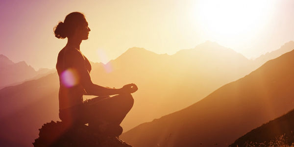 meditation at sunset against a backdrop of mountains