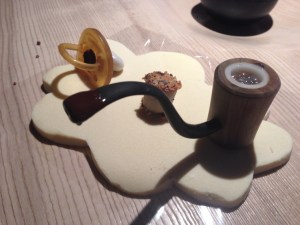 Pacifier filled with chocolate cream and pipe with rum and bubbles