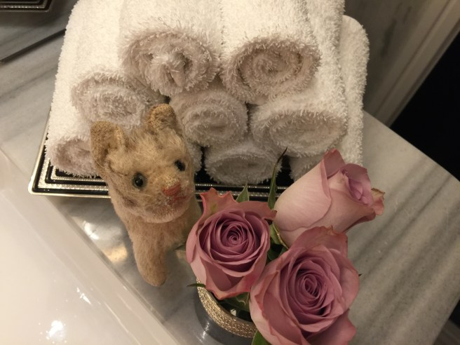 she liked the fluffy towels and flowers in the bathroom