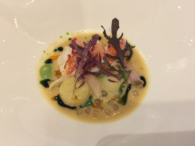 Grilled Maine lobster with smoked potato, ramps and shellfish-coconut nage